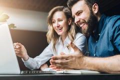 Коммерсантка и бизнесмен сидят на столе против компьтер-книжки и обсуждают проект дела, работая совместно Стоковые Изображения RF