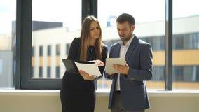 Коммерсантка и бизнесмен стоя в офисе и обсуждая идеи дела сток-видео