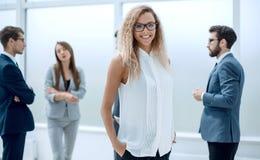 Коммерсантка и ее коллеги стоя в офисе стоковые изображения