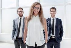 Коммерсантка и ее коллеги стоя в офисе стоковая фотография rf