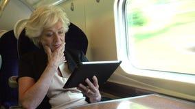 Коммерсантка коммутируя на поезде используя таблетку цифров сток-видео