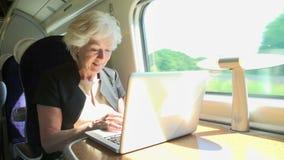 Коммерсантка коммутируя для работы на поезде и использовании видеоматериал