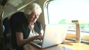 Коммерсантка коммутируя для работы на поезде и используя компьтер-книжку сток-видео