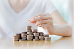 Коммерсантка кладя монетку к поднимая стогу монеток Стоковая Фотография RF