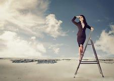 Коммерсантка на лестнице смотря далеко в пустыне Стоковые Фото