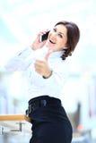 коммерсантка на телефоне и показывать tumbs вверх Стоковое фото RF