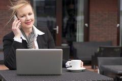 Коммерсантка на телефоне outdoors с компьтер-книжкой и чашкой кофе Стоковые Фото