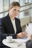 Коммерсантка обсуждая с коллегой во время перерыва на чашку кофе Стоковая Фотография RF
