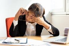 Коммерсантка отдыхая путем закрывать глаз пока работающ в офисе стоковое изображение