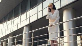 Коммерсантка перед офисным зданием говоря на сотовом телефоне видеоматериал