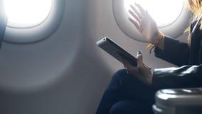Коммерсантка перемещение на юге сидя около окна и разговаривая с другом как раз на полете воздушных судн акции видеоматериалы