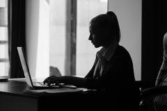 Коммерсантка печатая на компьтер-книжке на ее столе Стоковые Фотографии RF
