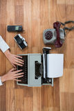 Коммерсантка печатая на машинке с винтажной камерой, телефоном и мобильным телефоном стоковые изображения