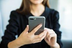 Коммерсантка печатая на телефоне или просматривает в интернете на работе в окружающей среде офиса стоковое фото