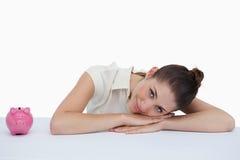 Коммерсантка полагаясь на ее столе с piggy банком Стоковое Изображение RF