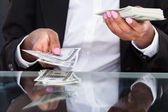 Коммерсантка подсчитывая долларовые банкноты на столе в офисе Стоковое Изображение RF