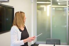 Коммерсантка представляя на встрече в современном офисе с видео стоковые фотографии rf
