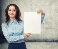 Коммерсантка представляя белый лист чистого листа бумаги Стоковое Фото
