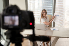 Коммерсантка представляя финансовый stats на камере Стоковые Изображения