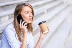 Коммерсантка принимая перерыв на чашку кофе и используя smartphone Стоковое фото RF