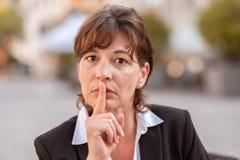 Коммерсантка при ее палец поднятый к ее губам стоковая фотография