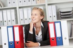 Коммерсантка при связыватели сидя на столе Стоковая Фотография