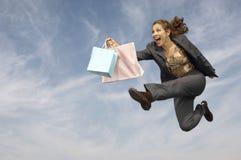 Коммерсантка при хозяйственные сумки бежать против облачного неба Стоковые Изображения