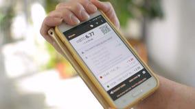 Коммерсантка проверяет баланс бумажника Bitcoin на экране smartphone мобильного телефона, ваша собственная концепция банка видеоматериал