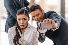Коммерсантка прыгает с веревочкой пока бизнесмен принимая selfie и кричащее в мегафоне стоковые фотографии rf