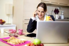Коммерсантка работая дома во время завтрака Стоковая Фотография