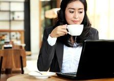 Коммерсантка работая на ее компьтер-книжке во время перерыва на чашку кофе Стоковое Изображение RF