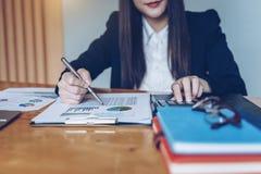 Коммерсантка работая на калькуляторе для того чтобы высчитать отчет о коммерческих информаций финансовый на деревянном столе стоковая фотография