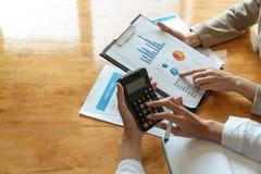 Коммерсантка работая на калькуляторе для того чтобы высчитать коммерческие информации финансовый отчет в конференц-зале стоковое изображение rf