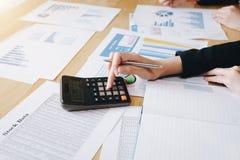 Коммерсантка работая на калькуляторе для того чтобы высчитать коммерческие информации финансовый отчет на таблице стоковая фотография rf