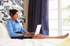 Коммерсантка работая на компьтер-книжке в гостиничном номере стоковые фотографии rf