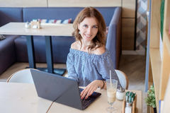 Коммерсантка работая на компьтер-книжке в кофейне Молодая бизнес-леди использует компьтер-книжку в кафе Печатать коммерсантки раб Стоковое Фото
