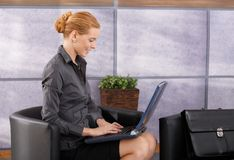 Коммерсантка работая на компьтер-книжке в лобби Стоковая Фотография RF