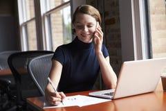 Коммерсантка работая на компьтер-книжке и звоня телефонный звонок Стоковые Фотографии RF