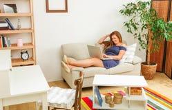 Коммерсантка работая на компьтер-книжке дома Стоковые Изображения