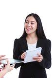 Коммерсантка разговаривая с некоторым телом и держа бумагу примечания, дальше Стоковое Изображение RF