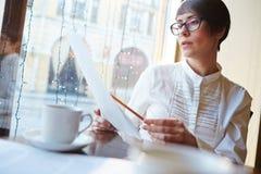 Коммерсантка рассматривая контракты в кафе Стоковые Изображения