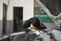 Коммерсантка расстроенная с автомобилем, голова на стороне автомобиля стоковые изображения