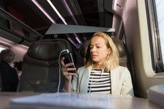 Коммерсантка связывая на мобильном телефоне пока путешествующ поездом Стоковое Изображение