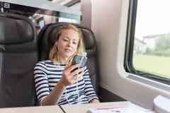 Коммерсантка связывая на мобильном телефоне пока путешествующ поездом Стоковые Фотографии RF
