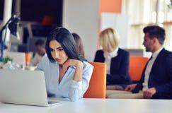 Коммерсантка сидит на столе перед компьютером Стоковое Фото