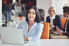 Коммерсантка сидит на столе перед компьютером Стоковая Фотография