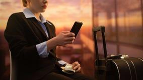 Коммерсантка сидя в аэропорте и используя приложение мобильного телефона для того чтобы сосчитать деньги для отключения сток-видео