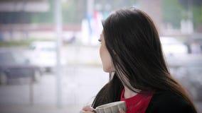 Коммерсантка сидя в кафе, работы конца-вверх привлекательная молодая на компьтер-книжке на фоне городского транспорта сток-видео