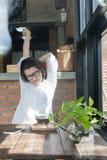 Коммерсантка сидя на ее месте работы и протягивая ее руки над ее головой Уставший женский работник на рабочем месте перед стоковое изображение