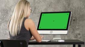 Коммерсантка сидя на ее столе в офисе работая на настольном мониторе Зеленый дисплей модель-макета экрана сток-видео